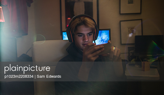 Teenage boy with headset using smart phone in dark bedroom - p1023m2208334 by Sam Edwards