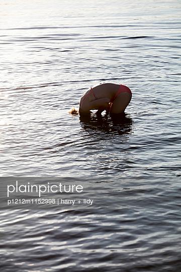 Mädchen taucht den Kopf in den See - p1212m1152998 von harry + lidy