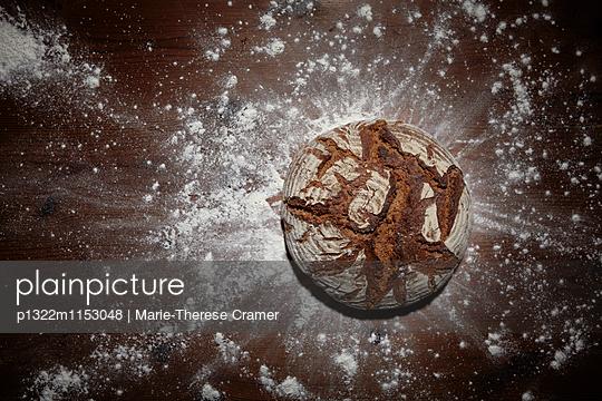 Runder Brotlaib auf einem Holztisch, umgeben von Mehl - p1322m1153048 von Marie-Therese Cramer