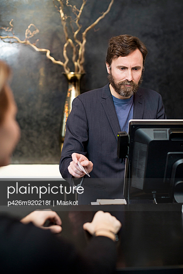 Male receptionist accepting payment through credit card from customer in hotel - p426m920218f by Maskot