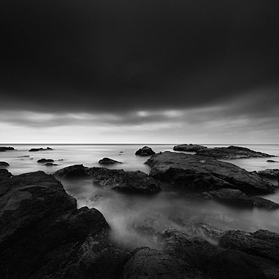 Long exposure of sea rocks and dramatic sky in Inamuragasaki, Kanagawa - p1166m2078142 by Cavan Images