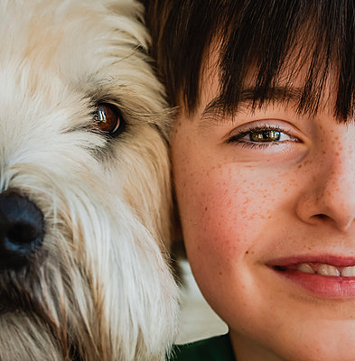 Close up of half of the faces of boy and his dog with heads together. - p1166m2169207 by Cavan Images