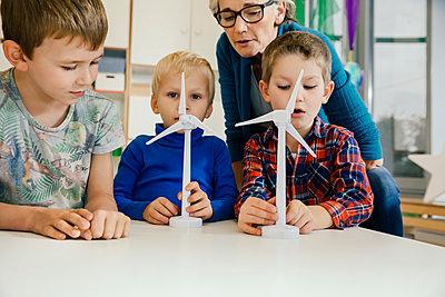 Boys and pre-school teacher looking at wind turbine models in kindergarten - p300m1537453 by Mareen Fischinger