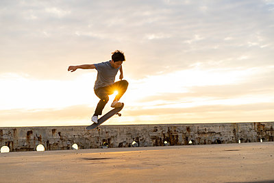 Young Chinese man skateboarding at sunsrise near the beach - p300m2012287 by VITTA GALLERY