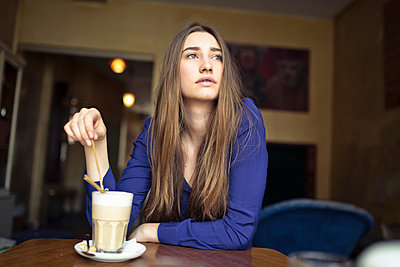 Young woman sitting at table in a cafe looking sideways - p300m2104470 by Philipp Nemenz