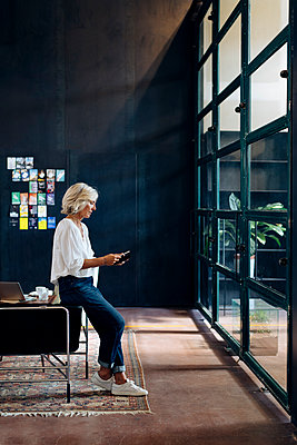 Casual mature businesswoman using smartphone in loft office - p300m2144468 by Sofie Delauw