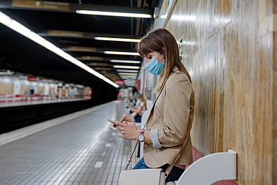 Woman with using mobile phone while sitting at subway platform during COVID-19 - p300m2264599 by Albert Martínez