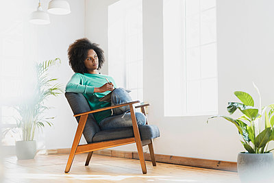 Woman day dreaming while sitting with book on armchair at home - p300m2277515 by Steve Brookland