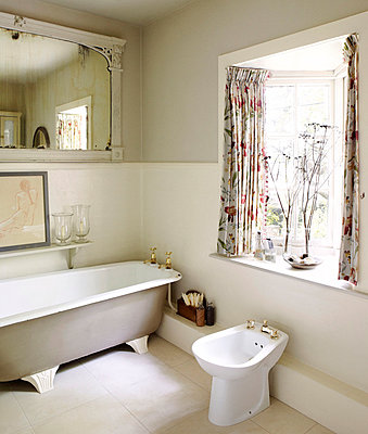 Bidet and freestanding bath in bathroom with floral patterned curtains on bay window - p349m790194 by Brent Darby