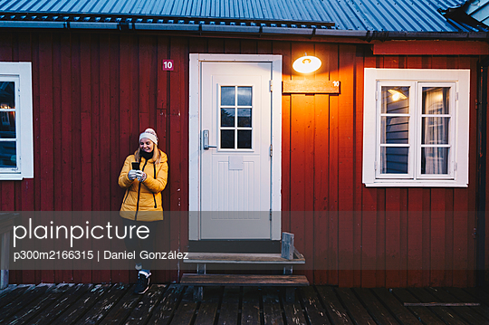 Tourist using smartphone at a hut in Hamnoy, Lofoten, Norway - p300m2166315 von Daniel González