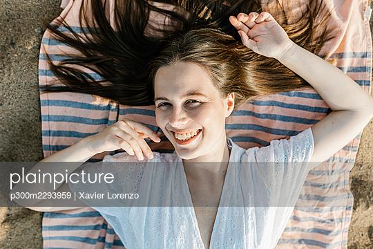 Smiling woman lying on beach towel - p300m2293959 by Xavier Lorenzo