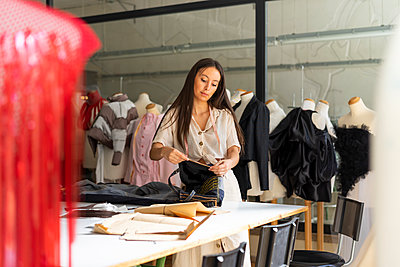 Young fashion designer working in her studio - p300m2012299 by VITTA GALLERY