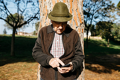 Spain, Barcelona. Senior man retired in a park with his hat resting on a tree and using the phone - p300m2167184 von Josep Rovirosa