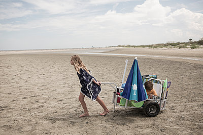 Girl pulling brother in cart on beach - p555m1522725 by Marc Romanelli