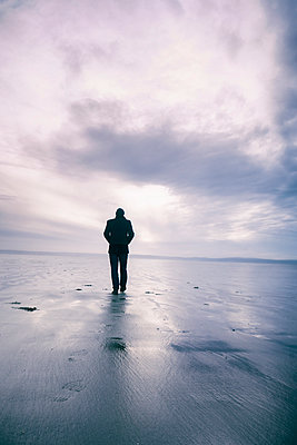 Rearview man walking on beach at low tide - p597m2150399 by Tim Robinson