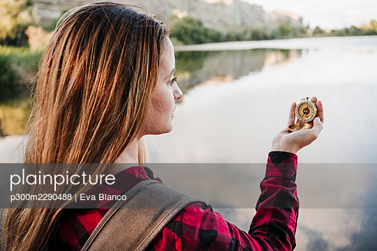 Young blond woman holding navigational compass at lakeshore - p300m2290488 by Eva Blanco