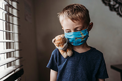 Close up of young school aged boy with mask on with stuffed animal - p1166m2207798 by Cavan Images