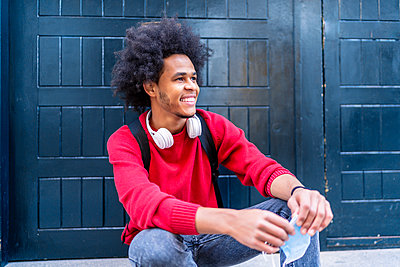 portrait of young man with afro hair smiling - p1166m2255126 by Cavan Images