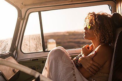 Pensive woman sitting in parked at sunset - p300m1505338 by Simona Pilolla
