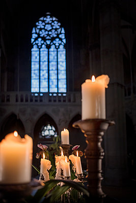 Lit candles against church window - p335m2177702 by Andreas Körner