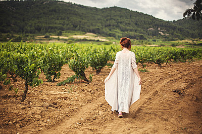 Young woman walking through vineyard, rear view, Boutenac, France - p924m1180257 by Lena Mirisola
