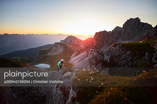 Woman climbing mountain ridge at Axamer Lizum, Austria - p300m2166294 by Christian Vorhofer