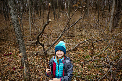 High angle portrait of girl holding dried branch while standing in forest - p1166m1486215 by Cavan Images