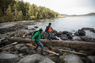 Father and son crossing rocks and fallen log on rugged beach - p1192m2000379 by Hero Images