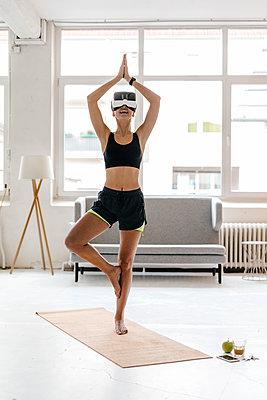 Young woman practising yoga wearing VR glasses - p300m1535146 by Kniel Synnatzschke
