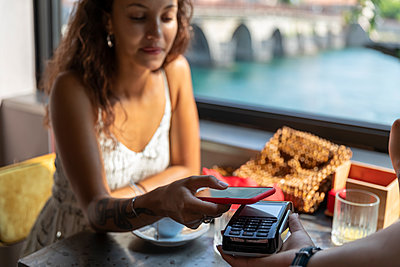 Young woman paying bill with smartphone at coffee shop - p300m2140905 by 27exp