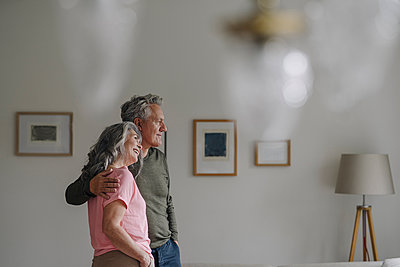 Senior couple standing in living room at home - p300m2156215 by Gustafsson