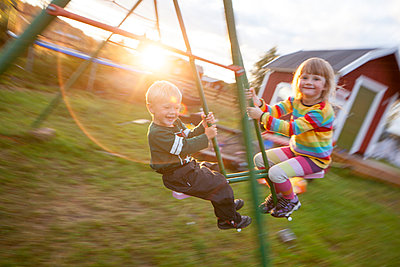 Boy and girl swinging, Norrbotten, Sweden - p312m926983f by Fredrik Ludvigsson