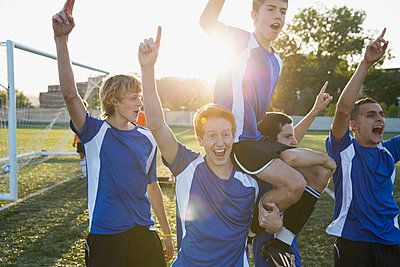 Soccer players cheering after a win. - p328m840884f by Hero Images