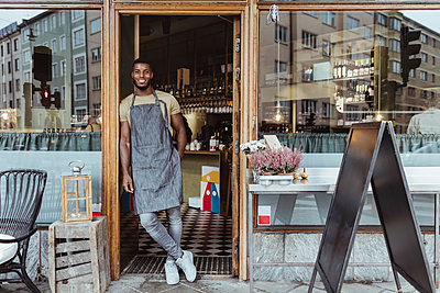 Smiling male owner leaning on doorway of delicatessen shop - p426m2270686 by Maskot