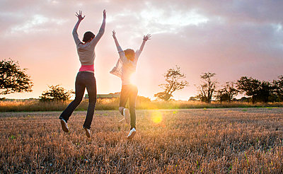 Two girls jumping for joy in sunlit field, rear view - p429m2077926 by Simon Potter