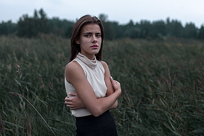 Caucasian teenage girl standing in field worrying - p555m1444277 by Vyacheslav Chistyakov