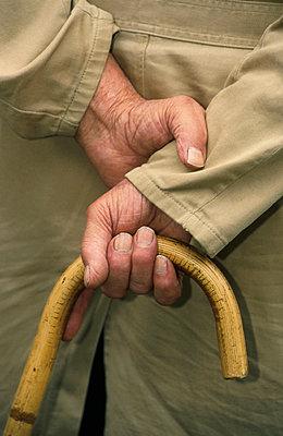 Senior man holding his walking stick - p8960779 by Frank Muller