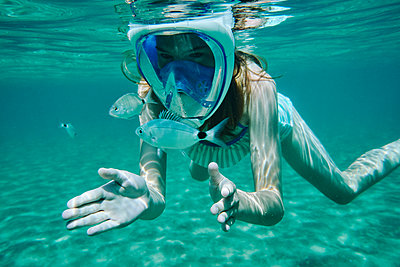 Underwater view of girl snorkelling, looking at fish, Limnos, Khios, Greece - p924m2097736 by Ross Woodhall