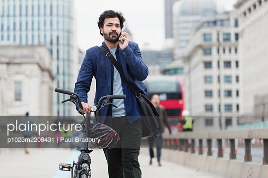 Businessman with bicycle talking on smart phone on city bridge - p1023m2208431 by Paul Bradbury