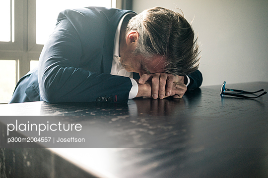 Mature businessman resting his head on the table - p300m2004557 von Joseffson