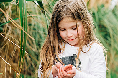 Young girl holding a small birds egg in her hands - p1166m2201898 by Cavan Images