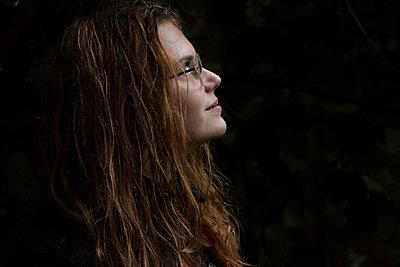 Junge Frau mit Brille blickt nach oben - p1650m2233711 von Hanna Sachau
