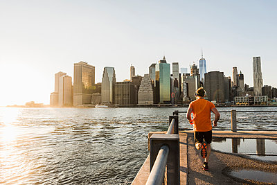 USA, Brooklyn, back view of man jogging in front of Manhattan skyline in the evening - p300m1205248 by Uwe Umstätter