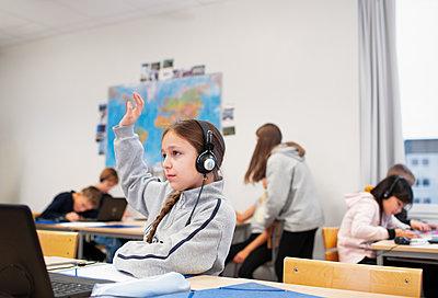 Girl raising hand in classroom - p312m2190347 by Scandinav