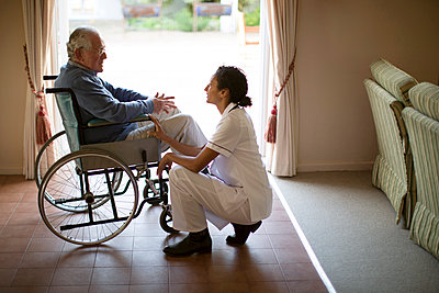 Nurse talking to patient in wheelchair - p555m1305752 by Resolution Productions