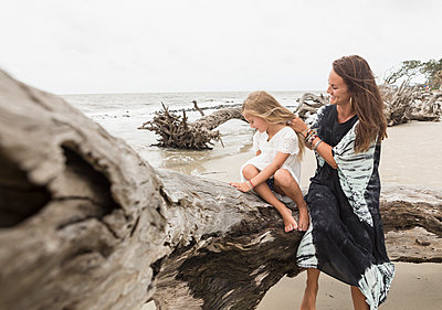 Caucasian mother and daughter sitting on driftwood on beach - p555m1504322 by Marc Romanelli