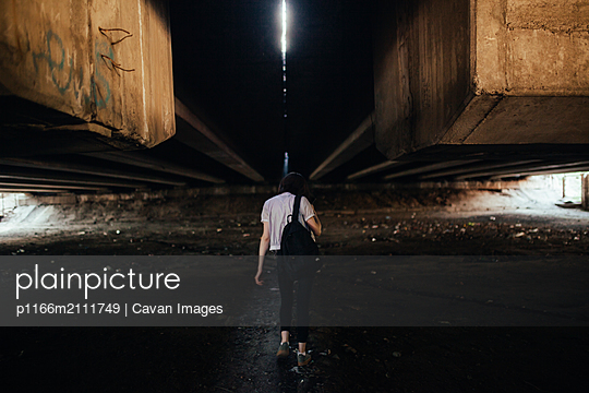 woman walks under a big bridge - p1166m2111749 by Cavan Images