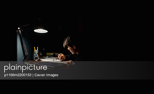 Teenage boy drawing at a desk in a dark room by lamp light. - p1166m2200153 by Cavan Images