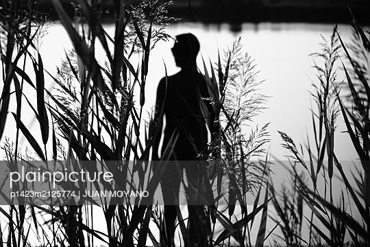 Nude man standing on the seashore of a lake - p1423m2125774 von JUAN MOYANO