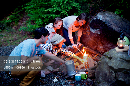 Friends roasting marshmallows over forest campfire - p555m1408956 by Shestock